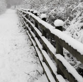 Snow covered footpath. Snow covered wooden fence alongside foothpath Stock Image