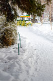 Snow-covered path under fir trees. In the distance, a colorful children`s train. Stock Photography