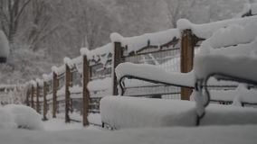 Snow covered patio furniture and garden fence. stock photo