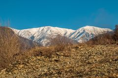Snow covered peaks at high landscape with dried stone ground foreground. Landscape photography Stock Photo