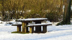 Snow Covered Picnic Table and Benches During Winter. A picnic table and benches covered in snow during the winter in the Netherlands Royalty Free Stock Photos