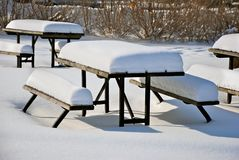 Snow covered picnic tables Royalty Free Stock Photo