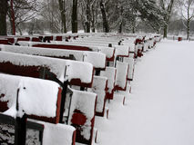 Snow covered picnic tables. Row of snow covered wooden picnic tables or benches stored in park Stock Images