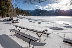 Snow covered picnic tables by frozen lake. Stock Photos