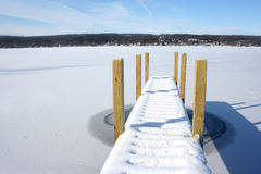 Snow covered pier on frozen lake with blue sky bey Royalty Free Stock Photography