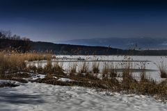 Snow covered pier near a lake, wintertime in Diosjeno, Hungary stock image