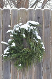 Snow covered pine juniper wreath wood fence gate Stock Photo