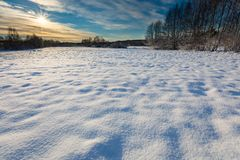 Snow covered polish landscape with rural road near fields and forest. Stock Image