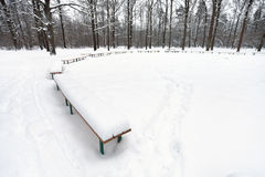 Snow covered public area with benches in city park Royalty Free Stock Photo