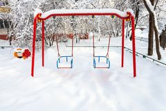 Snow-covered public kids swing in winter. Snow-covered public kids swing at residential district in Moscow city in winter morning Royalty Free Stock Photo