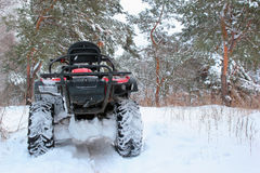 Snow covered quad bike in winter forest Stock Photo