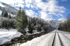 Snow covered railroad tracks in mountains royalty free stock image