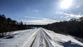 The snow-covered railway is lit by the sun. royalty free stock images