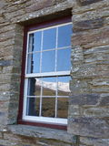 Snow covered range reflected in historic stone cottage window, New Zealand Royalty Free Stock Images