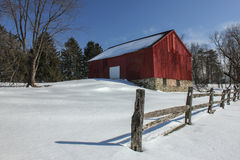 Snow Covered Red Barn and Split Rail Fence. Sunny snow covered field with small red barn accented by pine trees behind, split rail fence in front, and clear blue Stock Photos