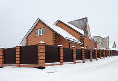 Snow covered red brick house with metal fence Stock Image