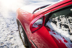 Snow covered red car parked outside, with focus on rear view mirror Stock Photo