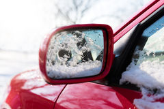 Snow covered red car parked outside, with focus on rear view mirror Royalty Free Stock Photo