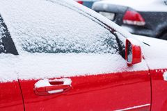 Snow-covered red car on parking in winter Stock Image