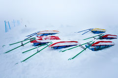 Snow-covered rescue sleds for injured skiers Stock Image