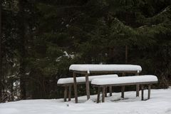 Snow covered resting place with table and benches. In the outdoors royalty free stock photography
