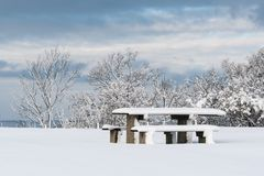 Snow covered resting place. With table and benches royalty free stock photo