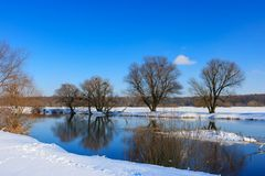 Snow-covered river bank on a sunny winter evening. Winter landscape Royalty Free Stock Photo