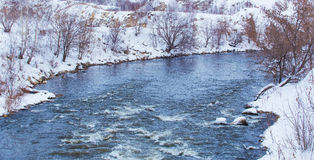 Snow-covered river bank in winter Royalty Free Stock Image