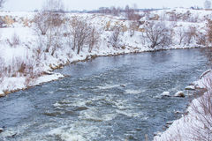 snow-covered river bank in winter Stock Images