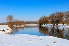 Snow-covered river bank at winter day sunset. Winter landscape Stock Photography