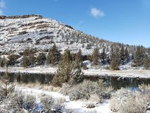 Snow covered river banks. The snow covered banks of the Crooked River with juniper trees and a hill in the background on a winter day in Central Oregon with stock photography
