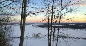 Snow-covered river in Russia. Chusovaya River, Perm region, Russia in January, covered with ice and snow. Sunset royalty free stock image