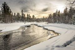 Snow-covered riverbank onder de zonsonderganghemel Noordelijk Karelië Rusland Stock Foto