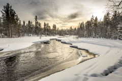Snow-covered riverbank under the sunset sky. Northern Karelia. Russia. Stock Photo
