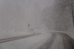 Snow-covered road in blizzard. Snowstorm. Winter time. Royalty Free Stock Photography
