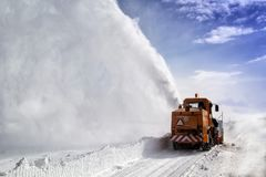 Snow-covered road cleaning by snow removal machine. Snow truck in highway royalty free stock images
