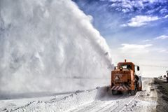 Snow-covered road cleaning by snow removal machine. Snow truck in highway royalty free stock photos