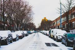 Snow Covered Road and Inline Parked Vehicles Between 2-storey Buildings Under White Sky royalty free stock photo