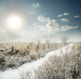 Snow-covered road past the fence in a field Royalty Free Stock Photos