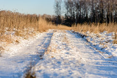 Snow-covered road receding into the distance. Road through a snowy field Stock Photos