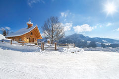 Snow covered road with wooden chapel Royalty Free Stock Photos