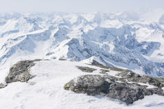 Snow covered rock with a mountain view in the back Royalty Free Stock Photography