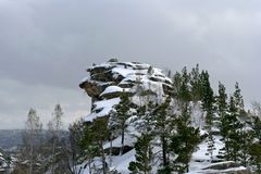 The snow-covered rock with pines Royalty Free Stock Image