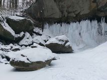Snow covered rocks at bottom of waterfall in cold January day. Snow covered rocks at bottom of waterfall in Williamsport Indiana on a cold January day Royalty Free Stock Image