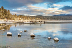 Snow covered rocks mountain lake and boat doc Stock Photo