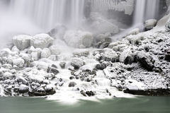 Snow covered rocks under large waterfall flowing into smooth aqu Royalty Free Stock Photos