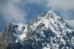 Snow covered rocky high mountain Stock Images