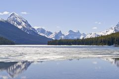 Rocky mountains reflecting in Maligne lake - Jasper national park, Canada. Snow covered Rocky mountains peaks reflected on the half frozen Maligne lake - Jasper Stock Images