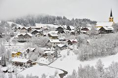 Snow-covered romantic German town landscape. View from the outskirts to the town Oberstaufen, richly covered in snow with fog descending at the edge of the Stock Photo