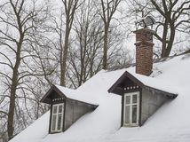 Snow covered roof with brick chimney and bay bow window with ici. Cles and bare tree background Royalty Free Stock Photos